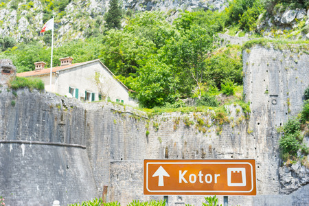 kotor: The sign KOTOR and fortress on background. Focus on sign. Kotor, Montenegro.