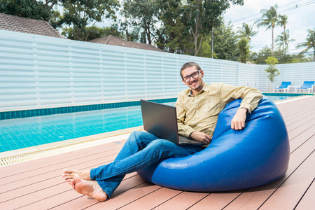 couching: Freelance businessman. Young handsome man in glasses working on laptop while sitting on the beanbag nearly swimming pool. Stock Photo