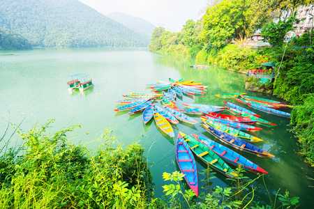 phewa: Colorful wooden boat at Fewa lake   in Pokhara, Nepal. Phewa lake is the major tourism spot for boating. Stock Photo