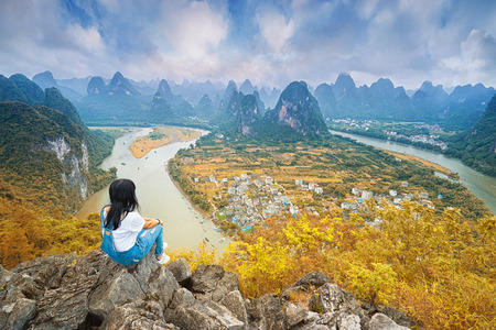 xing: Chinesse woman sitting on the top of mountain and enjoing view on valley with rocks. Xing Ping, Yangshuo, China. Stock Photo