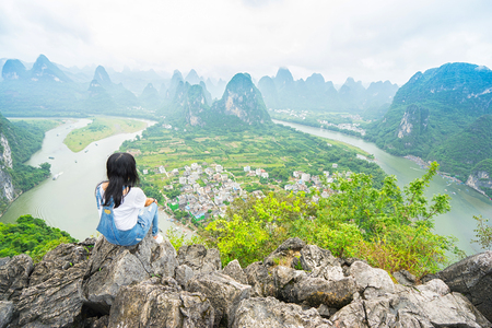 Young woman sitting on the top of mountain and enjoing view on valley with rocks. Xing Ping, Yangshuo, China.