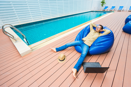 couching: Young excited man in glasses happy while sitting on the beanbag with hat  and laptop. Swimming pool on background.