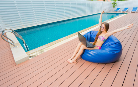 couching: Freelance businesswoman. Young smiling woman in bikini and glasses with laptop  and rised hands , sitting on blue beanbag. Swimming pool on background. Stock Photo