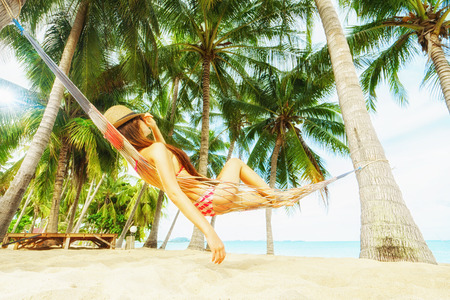 Vacation concept. Enjoying the summer. Young pretty woman in hat and sunglasses laying in hammock on the beach. Stock Photo