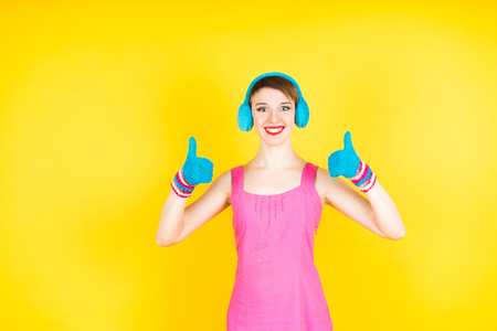 Smiling woman showing big thumbs  in gloves. Isolated on yellow background. Stock Photo
