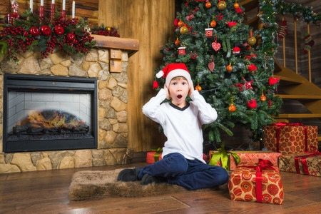 Young boy wearing a christmas hat dissapointed with gift. Merry Christmas and New Year concept.