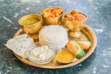 Traditional Nepalese food - thali (dal bhat) in a restaurant. Selective focus.  Standard-Bild