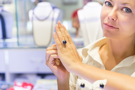 jewerly: Seller in jewerly shop showing ring with black pearl. Focus on pearl on the ring in hand.