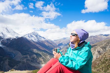 tibetian: Woman drinking tibetian tea and enjoing view on Himalayas mountains. Stock Photo