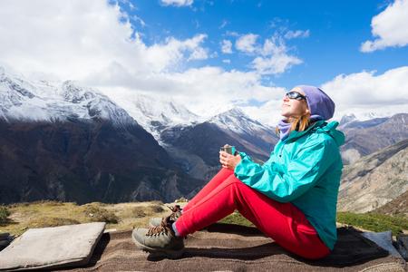 tibetian: Happy woman drinking tibetian tea and enjoing view on Himalayas mountains.
