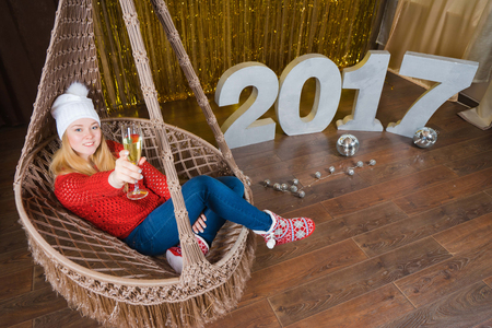Happy new year concept. Woman with glass of champagne on hammock and 2017 on the background.