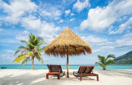 Wakacje w krajach tropikalnych. Leżaki, parasol i palmy na plaży.