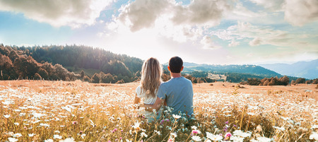 Couple sitting on the chamomiles field and looking at the cloudy sky. Back view. Banner Reklamní fotografie - 69376122