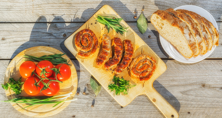 Assorted grilled sausages served on wooden plate with vegetables and bread on background. Banner.