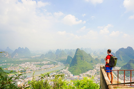 Hiker with backpack enjoying view from top of the hill with beautiful view on Yangshuo city with mountains around. Yangshuo, China.