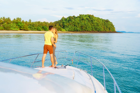 Romantic vacation and luxury travel. Young loving couple standing on the modern yacht deck. Sailing the sea. Stock Photo