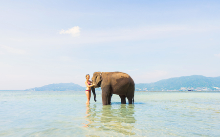 Happy girl  and elephant in the sea. Tropical vacation.