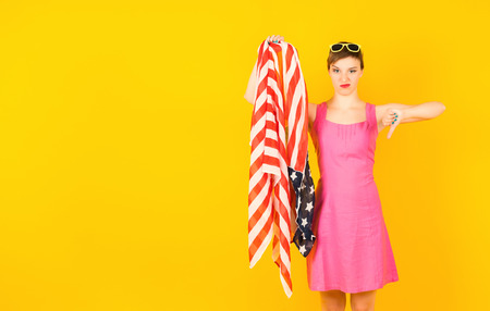 Woman with American flag in hand shows bad with another hand Stock Photo