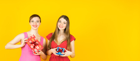 Two happy women with gift boxes on yellow background. Colorful studio banner.