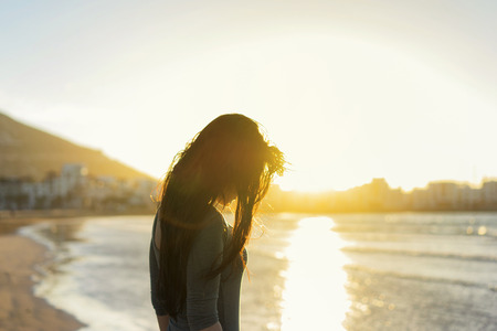 Silhouette of young girl in sunlight on the beach. Sunset time.