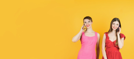 Technology, friendship and leirure concept - two smiling young women talking with smartphones. Isolated studio, yellow background, female model. Banner.