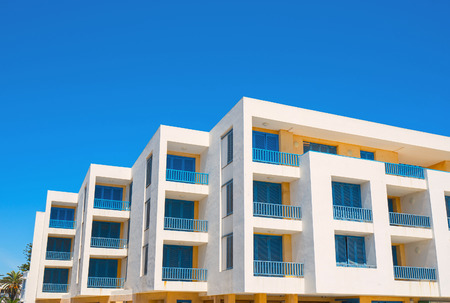 White living house with appartments and balconies in blue color. Stock Photo