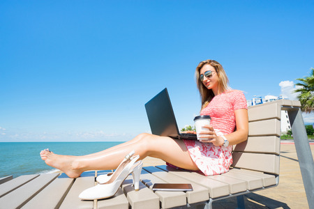 Woman sitting on the beach chiar  with laptop , smartphone, white shoes, and drink coffee.