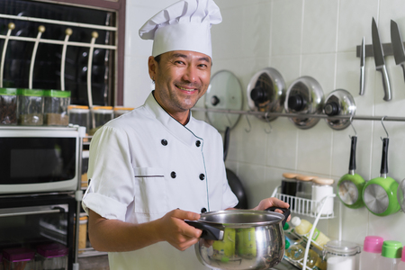 happy smiling male chef with the pan on kitchen background