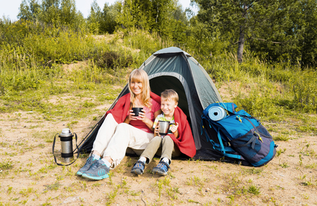 Happy  mother and son camping in tent and drinking tea on the nature.