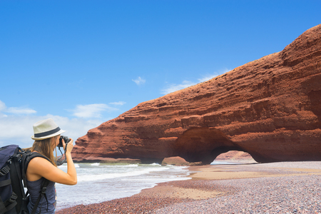 Tourist with backpack taking picture of rocks on Legzira beach, Morocco