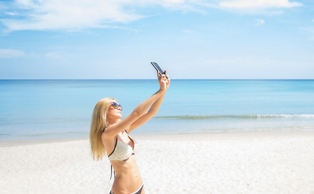 Young woman in swimwear taking selfie on the beach. Vacation concept.