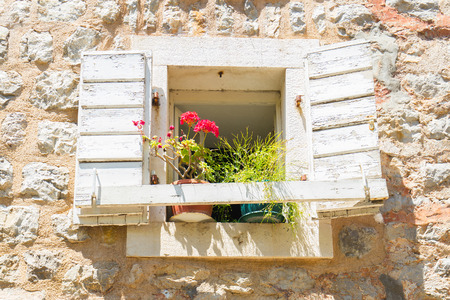 Window with flowers. Part of provencal house of small typical old town in Europe. Reklamní fotografie - 73194884