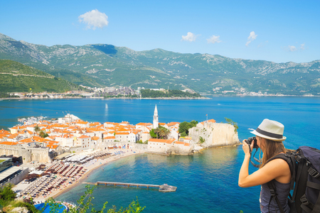 Tourist taking photo of old towt Budva from view point. Budva, Montenegro.