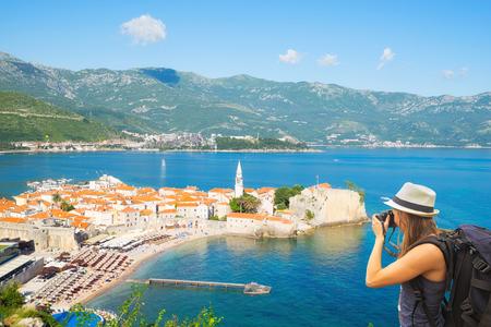 take a history: Tourist taking photo of old towt Budva from view point. Budva, Montenegro.
