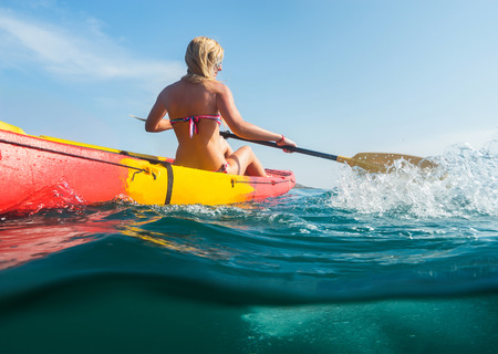 Woman on kayak in ocean with blue sky background. Split photo.
