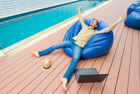Winner businessman. Young excited man in glasses happy while sitting on the beanbag with hat, smartphone and laptop. Swimming pool on background Reklamní fotografie