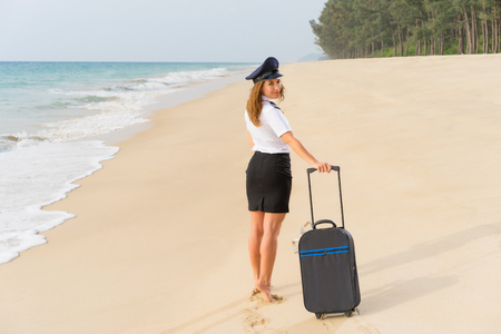 Travel concept. Young woman in flight attendant clothes walking on the beach with suitcase and hat .  Reklamní fotografie