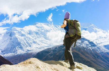 Travel concept. Hiker with backpack enjoing view on Himalayas mountains.