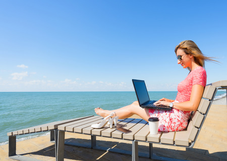 Young beautiful woman sitting on the beach chair with laptop , smartphone and shoes, and cup of coffee. Girl typing something on laptop. Reklamní fotografie