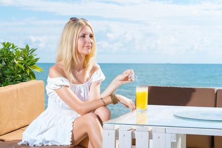 Portrait of young woman. Girl drinking juice in beach cafe with sky and sea background. Stock Photo