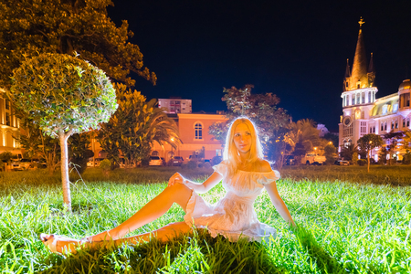 Young beautiful woman sitting on the grass at night time. Reklamní fotografie