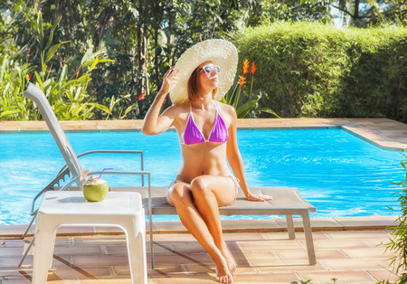 Young woman in swimwear and sunhat sunbathing nearly swimming pool. Vacation concept. Reklamní fotografie