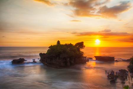 Sunset at Balis famous Tanah Lot temple, Indonesia. People and waves  in motion blur. Reklamní fotografie