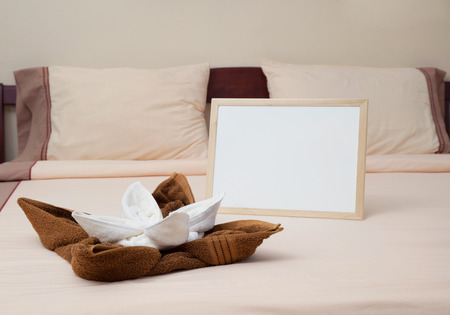 Hotel towels on the bed with white board for your text.  Reklamní fotografie