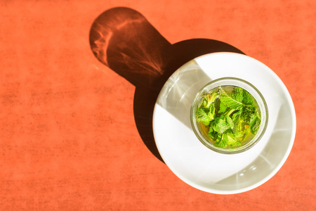 Traditional moroccan mint tea in glass on th table. Close up overhead photo. Focus on mint.