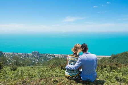 Young couple in love looking at sea from top of mountain.