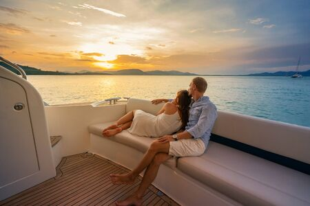Romantic vacation . Beautiful couple looking in sunset from the yacht.