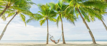 Woman lying on hammock between palms on the beautiful tropical beach. Travel and vacation concept. Banner and panoramic edition.