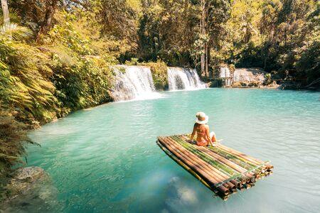 Woman in bikini and hat sitting on bamboo raft and enjoying view on waterfall.