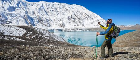 Travel and hikking concept: Trekker with backpack and smartphone on Tilicho lake. Snowly peaks of mountains and Tilicho lake on background. Banner edition. Standard-Bild